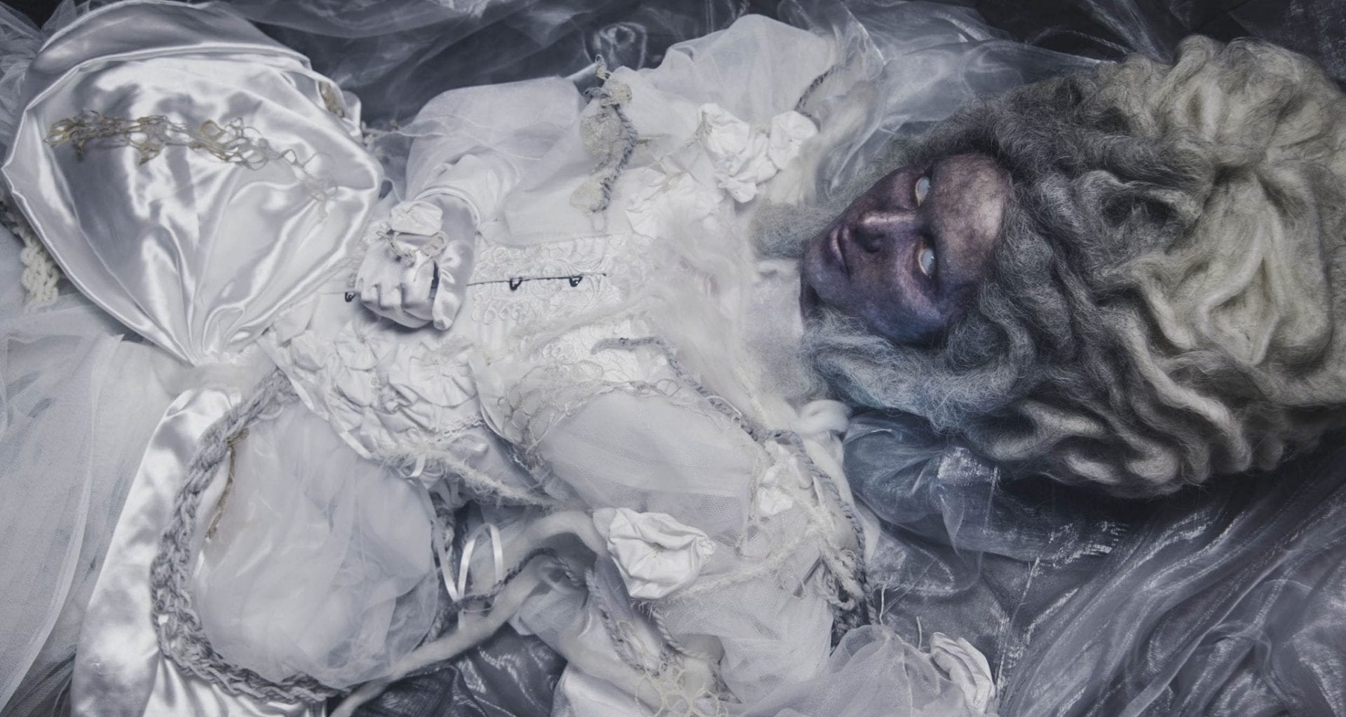 A woman lying down, styled with a matted, grey Elizabethan style wig. Glazed grey eyes and a visible vein-like skin texture