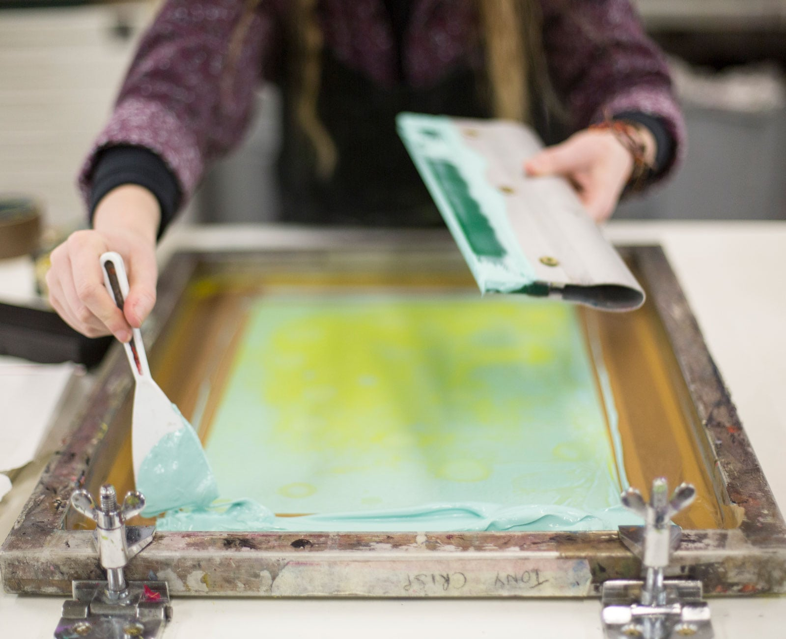 Student adding paint onto a screen print
