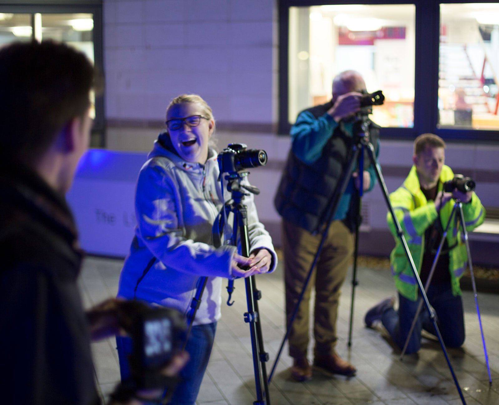 Students using cameras on tripods at night time