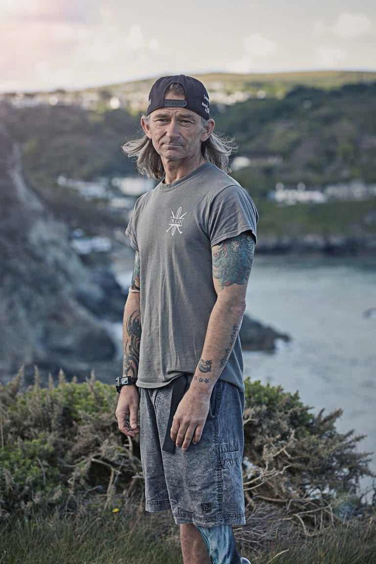 Older looking man with tattoos and backwards hat in foreground, with the cliffs and sea in background.
