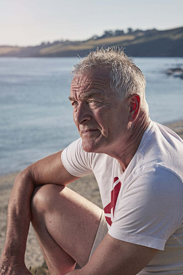 Older man in white t-shirt sat down, resting his arm on his knee in the foreground. Coastline and the sea can be seen in the background.