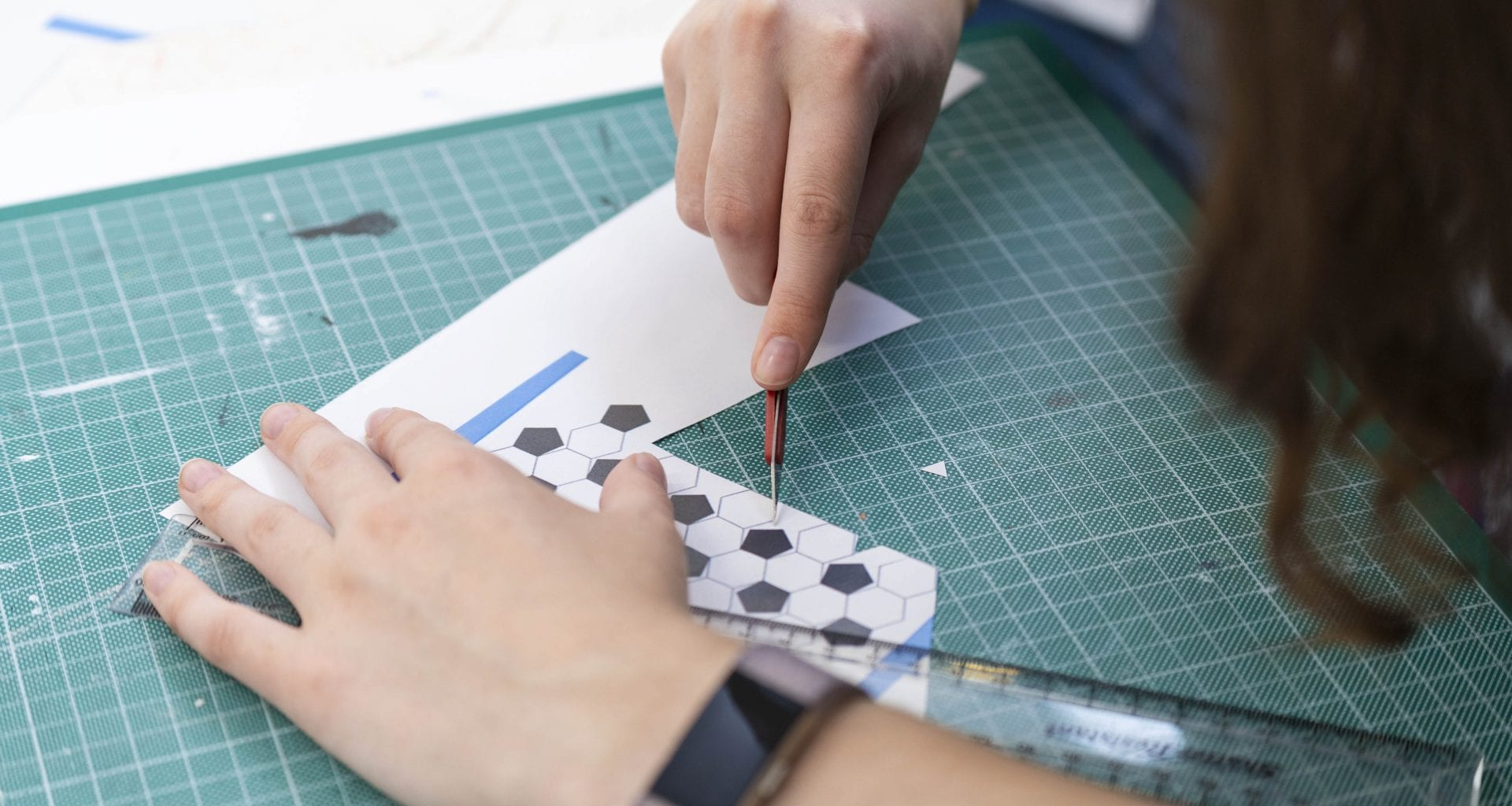 Image of a student using an exacto knife to cut out shapes