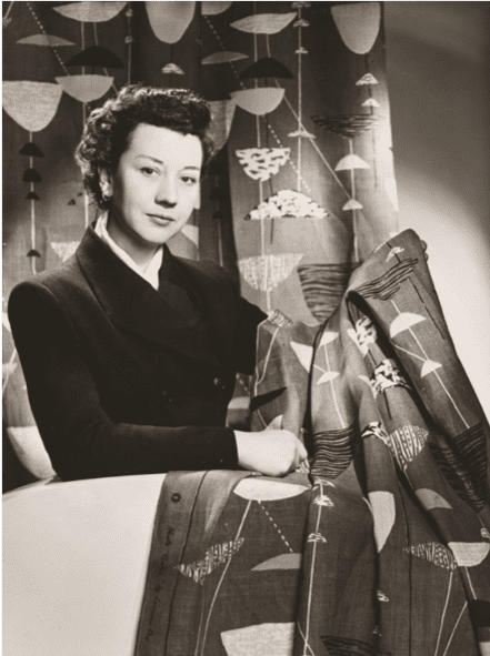Lucienne Day poses with a sample of her material design work.