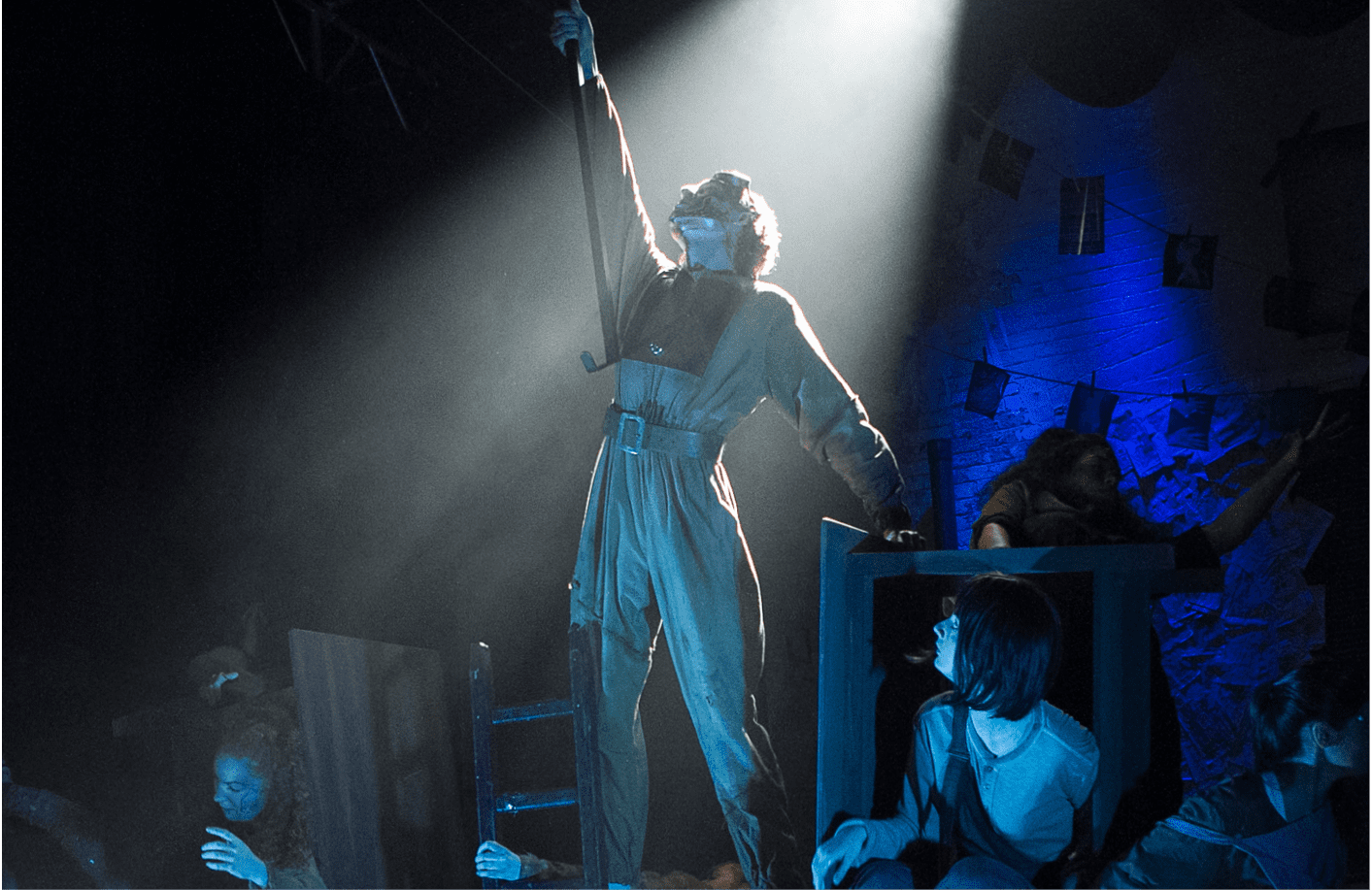 an acting student standing on stage with blue lighting and a spotlight beaming down on them. Their right hand is raised. There are other actors crouching down and looking up at them.